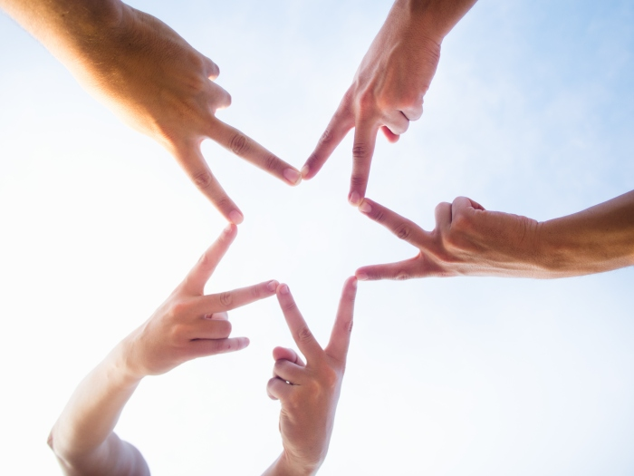 Five friends uniting their hands to make a star